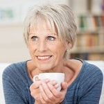 lady smiling with teacup cupped in hands
