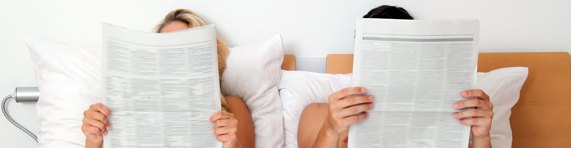 couple in bed reading newspapers
