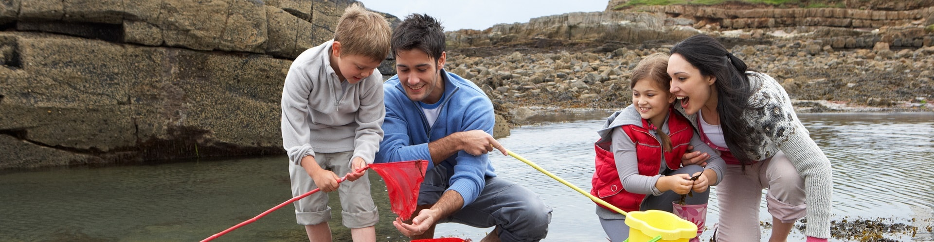 young family at beach fishing in rock pools